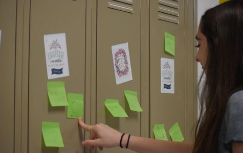 Eighth grader Keira Moran adds a positive post it note to a student's locker during an activity to spread positivity. Photo by Andrew Brackett