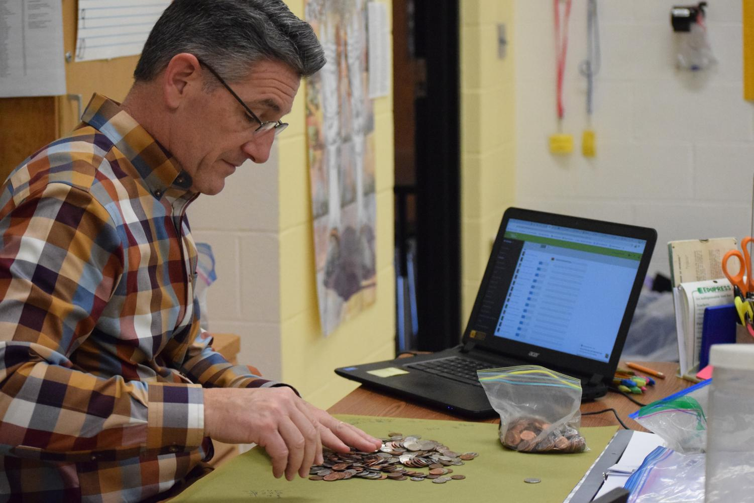Mr. Larry Richmond counts the coins for the fundraiser.